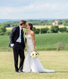 Bride in a Berta Bridal gown kisses groom in a navy Ralph Lauren tuxedo on a Pennsylvania field