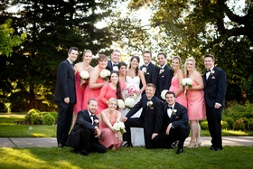 Bride and groom with bridesmaids in pink dresses and groomsmen in black tuxedos at a country club