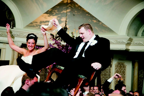 Bride in a Monique Lhuillier gown and groom in a black tuxedo dance the hora