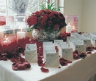 Escort card table with red roses and hurricane candles
