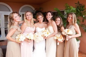 Bride with girlfriends wearing floor-length gowns