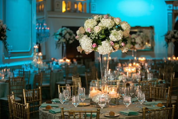 Ballroom with blue lighting and tall flowers