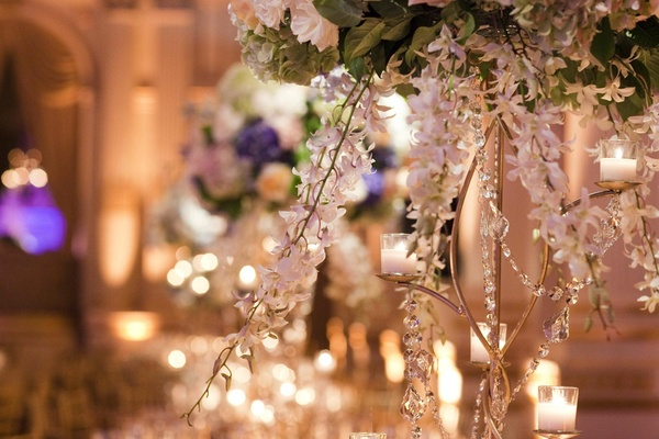Wedding centerpiece with white orchid stems, candles and crystal stands