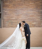 Bride and groom kiss in front of brick wall in NYC