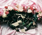 Pink and ivory flowers tied with brown ribbons