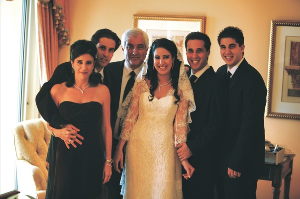 Bride in a Liancarlo lace dress and mantilla veil with her family in black attire