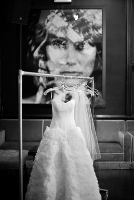 Black and white photo of wedding dress on rolling rack
