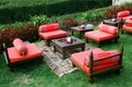 Outdoor seating with red pillows and rugs
