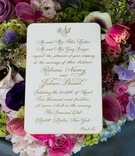 White wedding invitation with gold calligraphy in a bed of colorful flowers