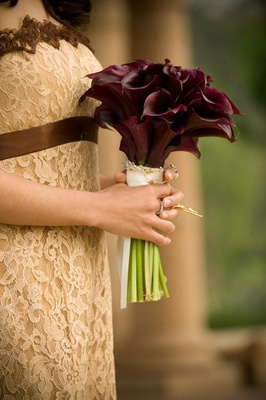 Bridesmaid holding bouquet of burgundy calla lilies