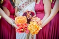 Bridesmaids hold bouquets of yellow and orange flowers