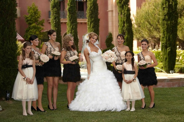 Bridesmaids in pink and feather black gowns