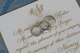 Bride's diamond engagement ring and wedding band and groom's platinum wedding band on invitation