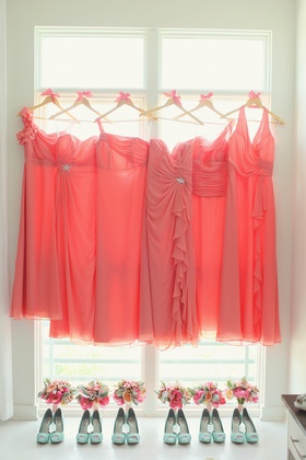Bridesmaid dresses in different styles on hangers above mint heels and bouquets