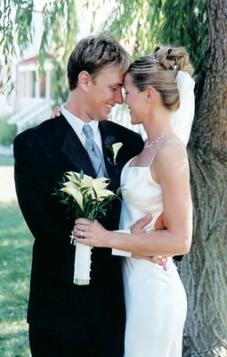 Bride in sleek dress hugs groom while holding bouquet