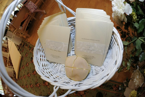 White basket holding ivory wedding programs