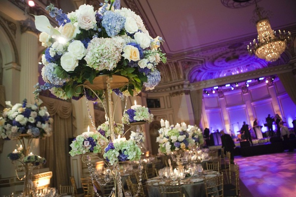 Wedding reception centerpiece of golden stands with white, blue, and green flowers