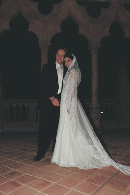 Bride in a Liancarlo lace dress and mantilla veil with groom in a black tuxedo and striped tie