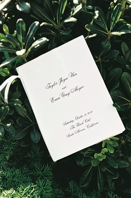wedding program with calligraphy and ribbon