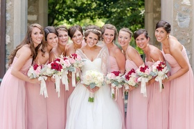 Bride with bridesmaids in pink gowns and summer bouquets