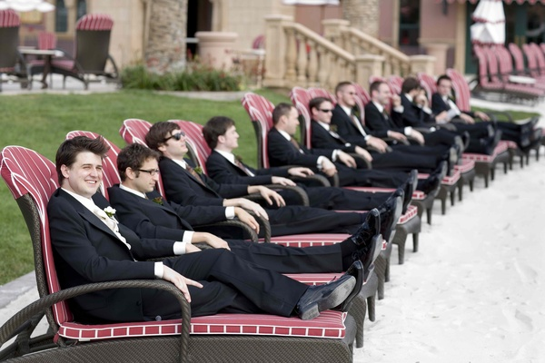 Men in tuxedos relaxing on pool chairs