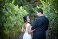 Bride in a cap sleeve lace gown walks among vineyard with groom in a dark suit