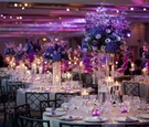 Crystal vases topped with blue and purple flowers