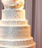 White wedding cake with a lace design and fresh flowers