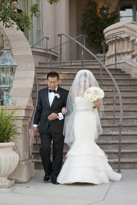 Asian dad and bride walk down stairs before ceremony