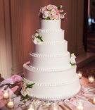 White wedding cake with beading and fresh roses