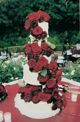 Red roses cascade down the sides of cake
