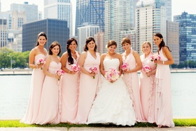 bride and bridesmaids wearing pink gowns in front of chicago skyline