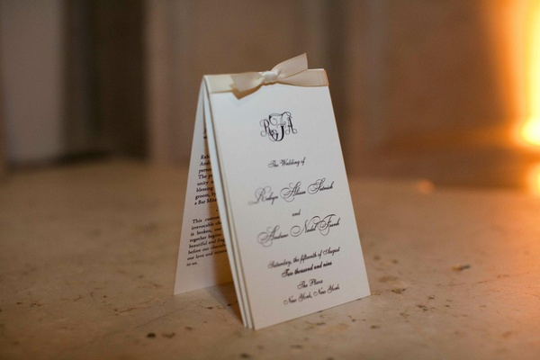White wedding invitation with a cream ribbon