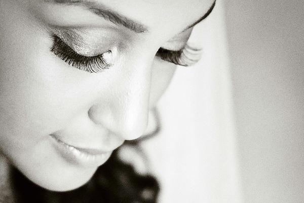 Black and white photo of bride in fake eyelashes