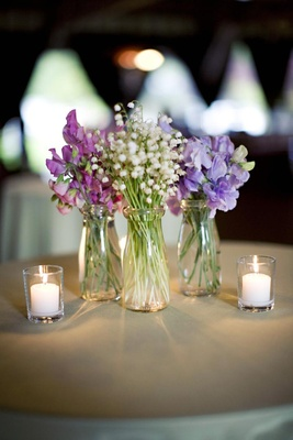 small glass jars filled with single-variety purple and white flowers