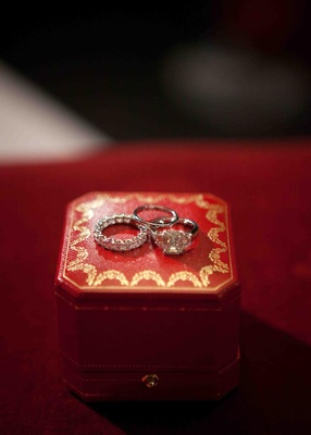Engagement ring and wedding rings on red and gold jewelry box