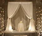 Wedding ceremony with candles and orchid strands lining an aisle to a chuppah