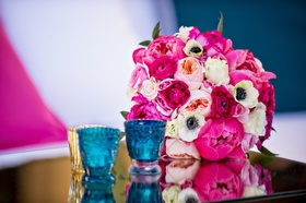 Pink peony, peach rose, ranunculus flowers, and anemone bouquet on mirror table