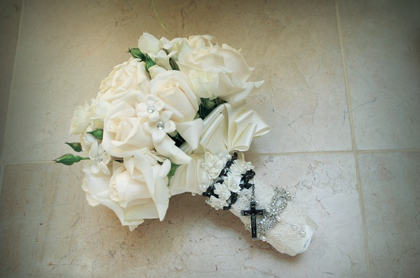 All-white flowers wrapped in lace and rosary