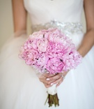 Bride holding garden roses or peonies wrapped in white