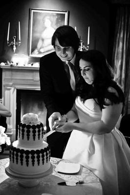 Black and white photo of bride and groom cutting two layer cake