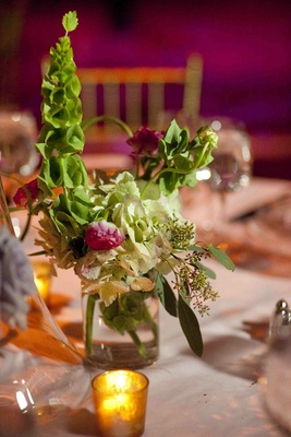 Wedding reception table with green and red flowers
