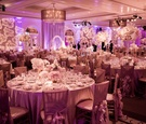 Violet and rose lighting on round guest tables