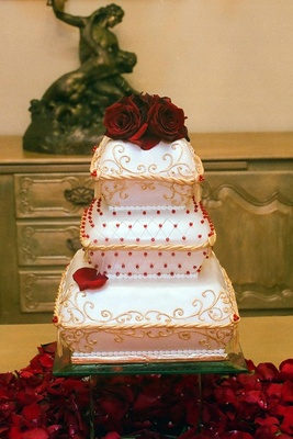 White, red, and gold wedding cake with roses