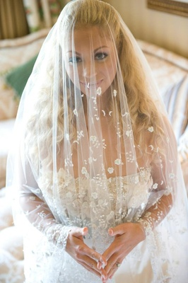 Bride wearing veil over her face with flowers